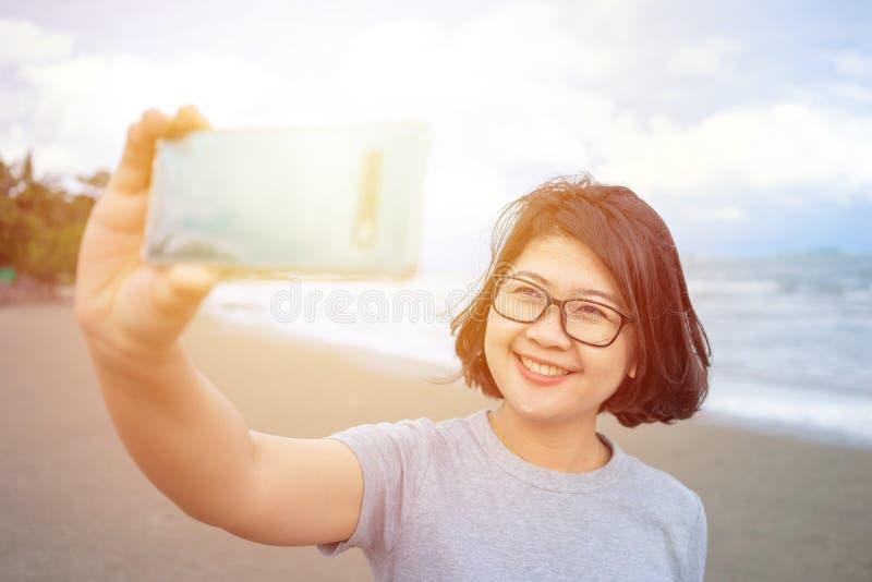 Όμορφη νέα γυναίκα που κρατά ένα smartphone Προκειμένου να ληφθεί μια εικόνα σας από ένα τηλέφωνο Selfie καμερών : στοκ φωτογραφίες