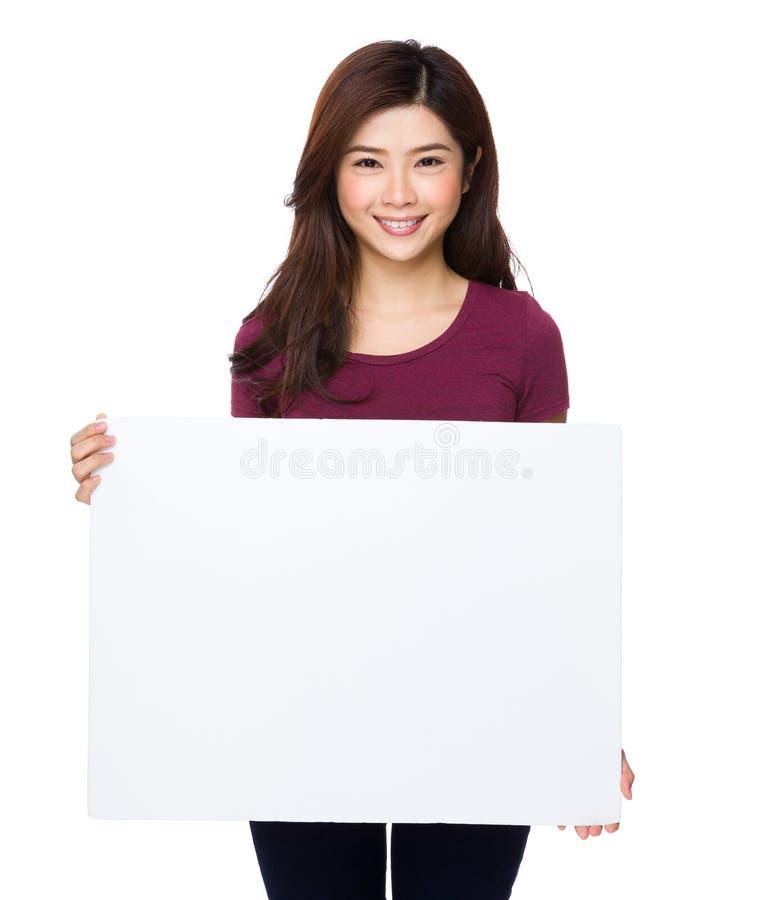 Όμορφη νέα γυναίκα που κρατά τον κενό πίνακα διαφημίσεων στοκ εικόνες