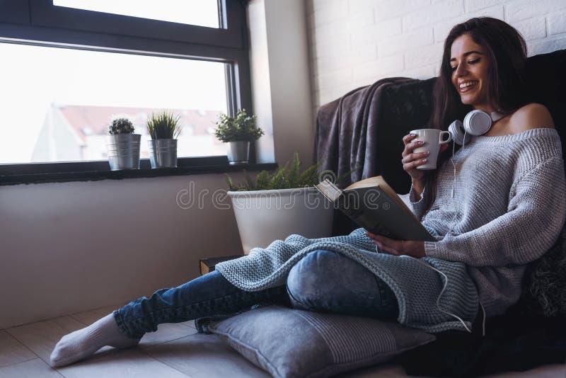 Όμορφη νέα γυναίκα που πίνει στο σπίτι τον καφέ που διαβάζει ένα βιβλίο στοκ φωτογραφίες