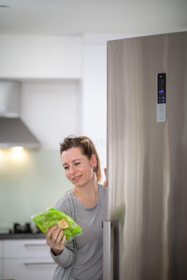 Όμορφη, νέα γυναίκα που παίρνει τα παντοπωλεία από το ψυγείο, που ελέγχει τις ημερομηνίες στοκ εικόνα