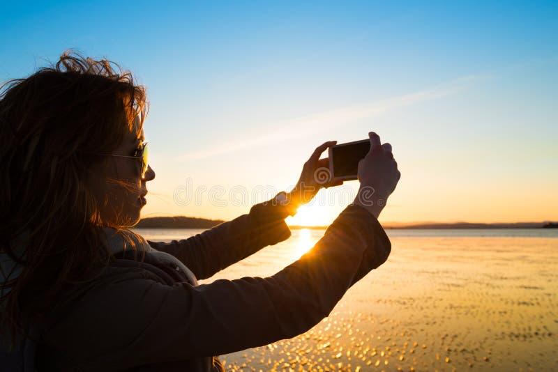 Όμορφη νέα γυναίκα που παίρνει την εικόνα της, selfie, σε μια παραλία στοκ φωτογραφίες