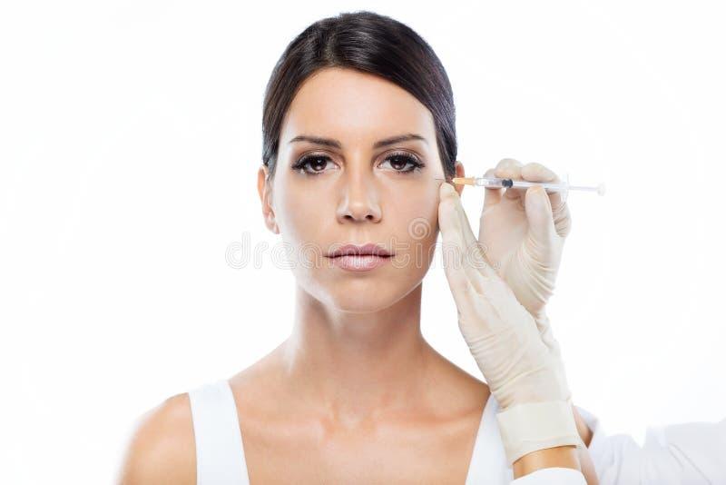 Όμορφη νέα γυναίκα που παίρνει botox την καλλυντική έγχυση στο πρόσωπό της πέρα από το άσπρο υπόβαθρο στοκ φωτογραφία με δικαίωμα ελεύθερης χρήσης