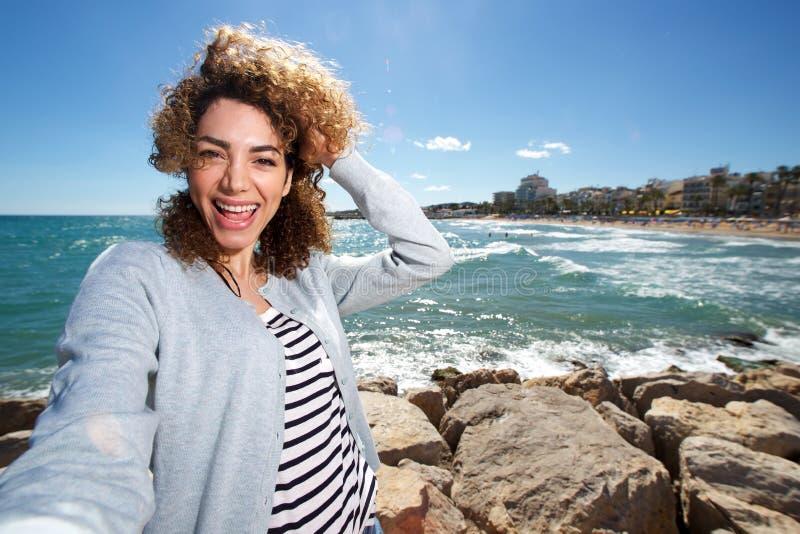 Όμορφη νέα γυναίκα που παίρνει selfie από την παραλία στοκ εικόνες