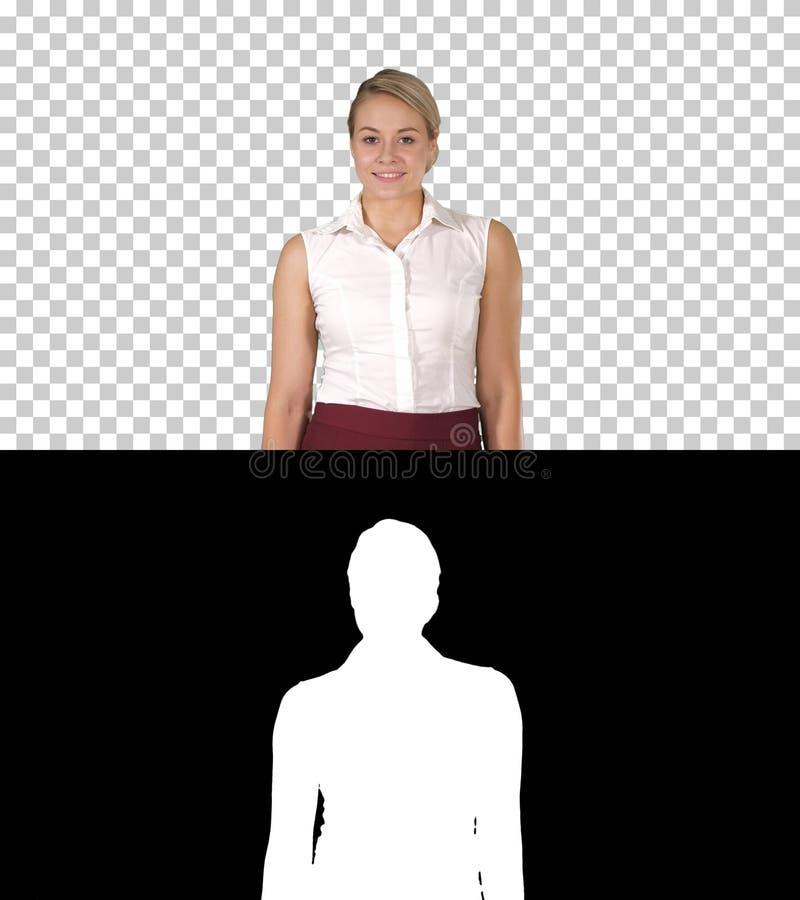 Όμορφη νέα γυναίκα που περπατά προς τη κάμερα και που χαμογελά, άλφα κα στοκ φωτογραφία