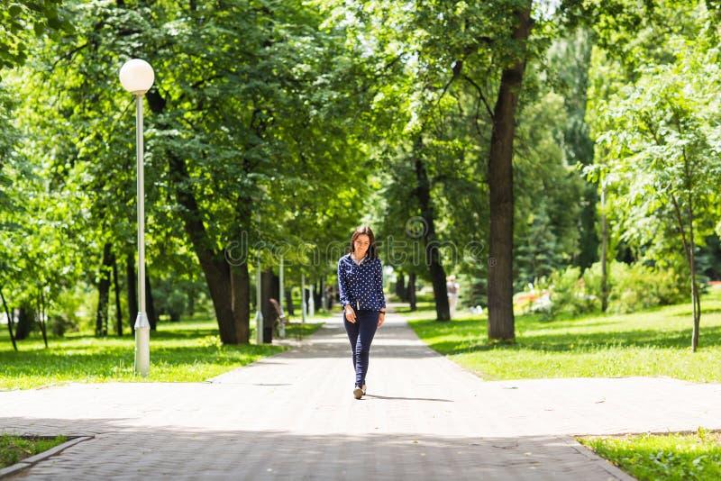 Όμορφη νέα γυναίκα που περπατά στο πράσινο θερινό πάρκο στοκ φωτογραφία