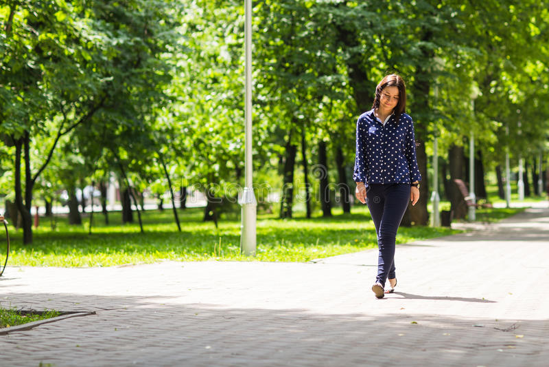Όμορφη νέα γυναίκα που περπατά στο πράσινο θερινό πάρκο στοκ εικόνες