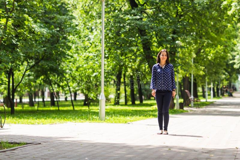 Όμορφη νέα γυναίκα που περπατά στο πράσινο θερινό πάρκο στοκ φωτογραφία με δικαίωμα ελεύθερης χρήσης