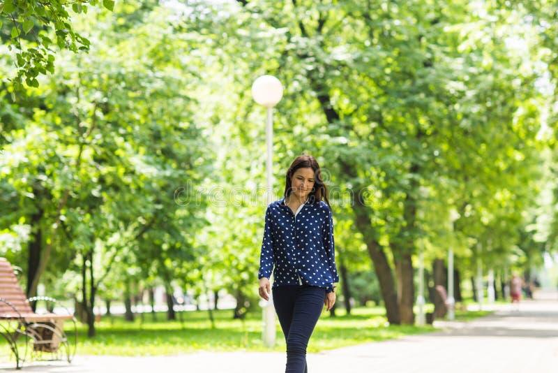 Όμορφη νέα γυναίκα που περπατά στο πράσινο θερινό πάρκο στοκ εικόνες με δικαίωμα ελεύθερης χρήσης