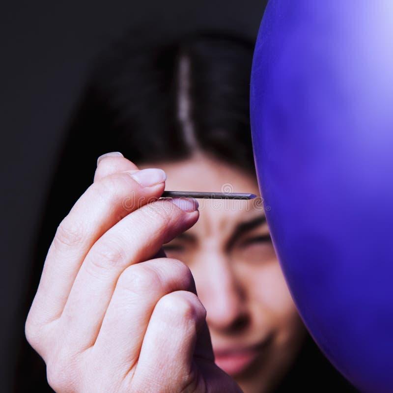 Όμορφη νέα γυναίκα που προετοιμάζεται να σκάσει το μπαλόνι ως σύμβολο του Di στοκ εικόνες