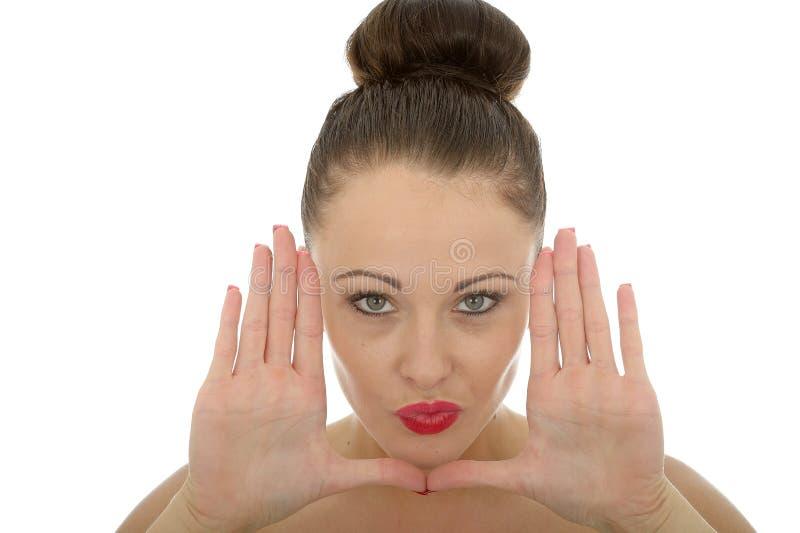 Όμορφη νέα γυναίκα που πλαισιώνει το πρόσωπό της με τα χέρια της που φαίνονται εκτάρια στοκ εικόνα με δικαίωμα ελεύθερης χρήσης