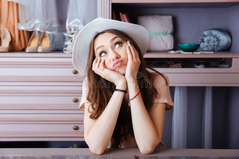 Όμορφη νέα γυναίκα που σκέφτεται για κάτι στο ντουλάπι της στοκ φωτογραφίες
