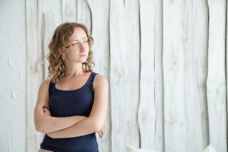 Όμορφη νέα γυναίκα που στέκεται με τα διασχισμένα όπλα ενάντια στον γκρίζο τοίχο στοκ εικόνα με δικαίωμα ελεύθερης χρήσης