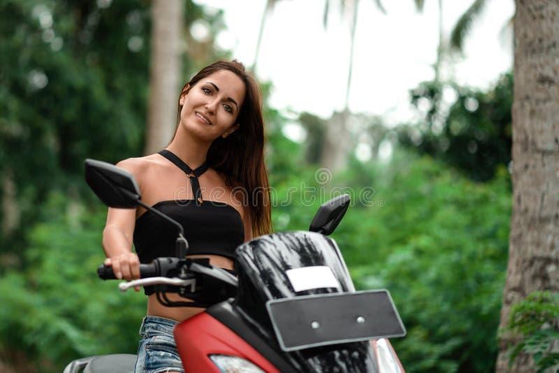 Όμορφη νέα γυναίκα που ταξιδεύει σε ένα μηχανικό δίκυκλο στοκ εικόνες