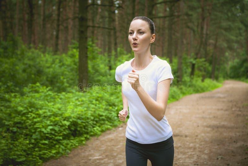 Όμορφη νέα γυναίκα που τρέχει στο πράσινο πάρκο την ηλιόλουστη θερινή ημέρα στοκ εικόνες