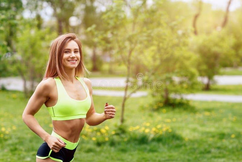 Όμορφη νέα γυναίκα που τρέχει στο πράσινο πάρκο στοκ εικόνα με δικαίωμα ελεύθερης χρήσης