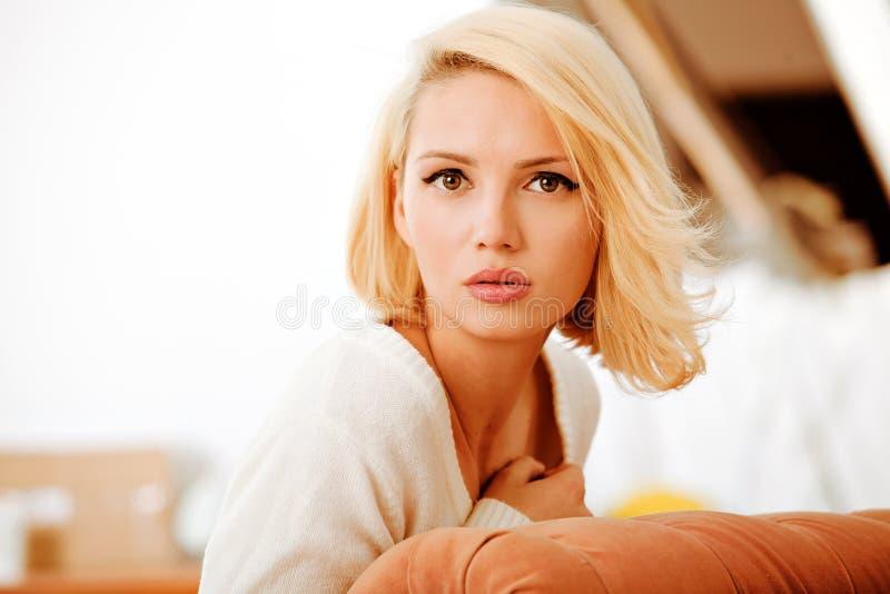 Όμορφη νέα γυναίκα, που φορά ένα άσπρο πουλόβερ στοκ φωτογραφία