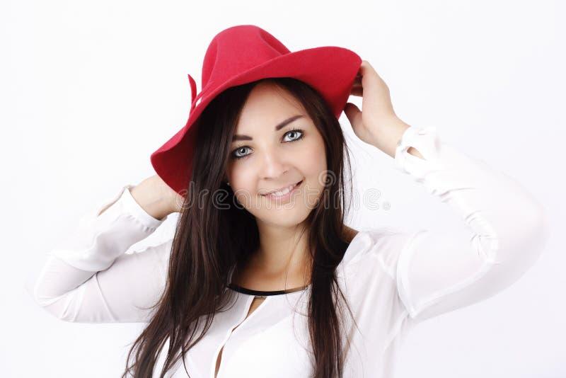 Όμορφη νέα γυναίκα που φορά το κόκκινο καπέλο στοκ εικόνες