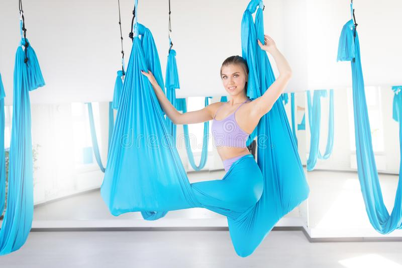 Όμορφη νέα γυναίκα που χαμογελά στην άσκηση της γιόγκας μυγών aero στο άσπρο στούντιο στις μπλε αιώρες Τέντωμα έννοιας στοκ φωτογραφία