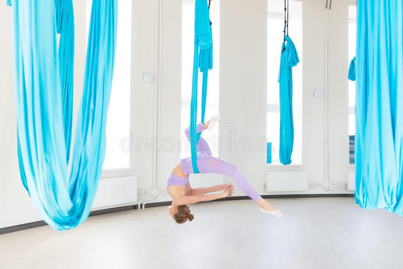 Όμορφη νέα γυναίκα που χαμογελά στην άσκηση της γιόγκας μυγών aero στο άσπρο στούντιο στις μπλε αιώρες Τέντωμα έννοιας στοκ φωτογραφία με δικαίωμα ελεύθερης χρήσης