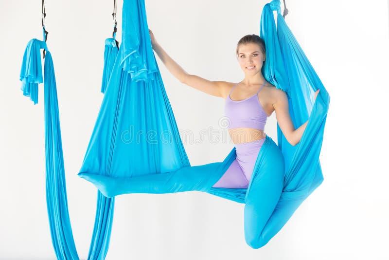 Όμορφη νέα γυναίκα που χαμογελά στην άσκηση της γιόγκας μυγών aero στο άσπρο στούντιο στις μπλε αιώρες Τέντωμα έννοιας στοκ εικόνες