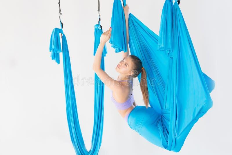 Όμορφη νέα γυναίκα που χαμογελά στην άσκηση της γιόγκας μυγών aero στο άσπρο στούντιο στις μπλε αιώρες Τέντωμα έννοιας στοκ φωτογραφίες