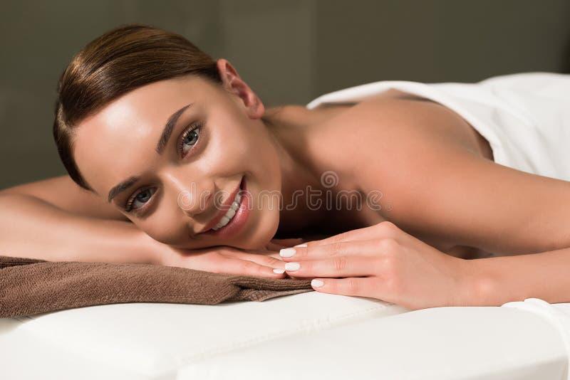 όμορφη νέα γυναίκα που χαμογελά στη κάμερα στον πίνακα μασάζ στοκ εικόνα