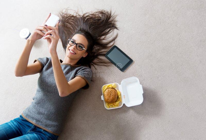 Όμορφη νέα γυναίκα που χρησιμοποιεί ένα τηλέφωνο κυττάρων στοκ φωτογραφία με δικαίωμα ελεύθερης χρήσης