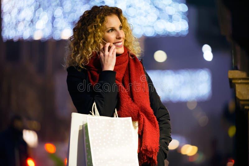 Όμορφη νέα γυναίκα που χρησιμοποιεί το κινητό τηλέφωνό της στην οδό τη νύχτα στοκ εικόνες