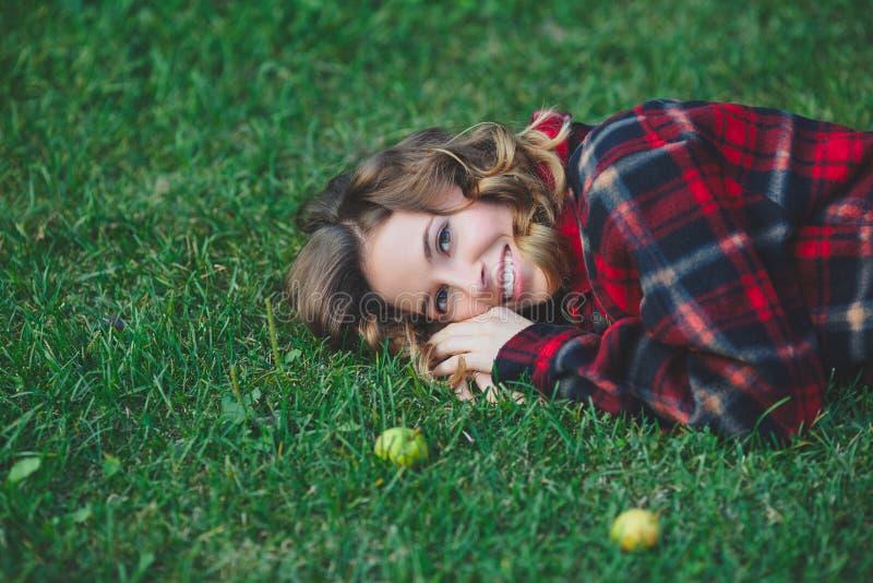 Όμορφη νέα γυναίκα σε ένα αρσενικό πουκάμισο φανέλας που βρίσκεται στην πράσινη χλόη στοκ φωτογραφίες