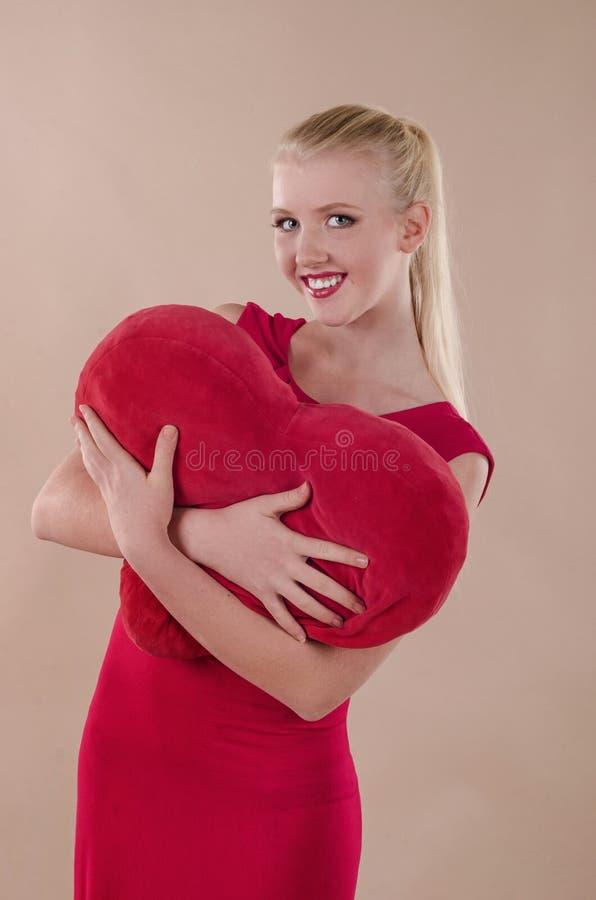 Όμορφη νέα γυναίκα σε ένα φωτεινό κόκκινο κρυψίνους φόρεμα στοκ φωτογραφία με δικαίωμα ελεύθερης χρήσης