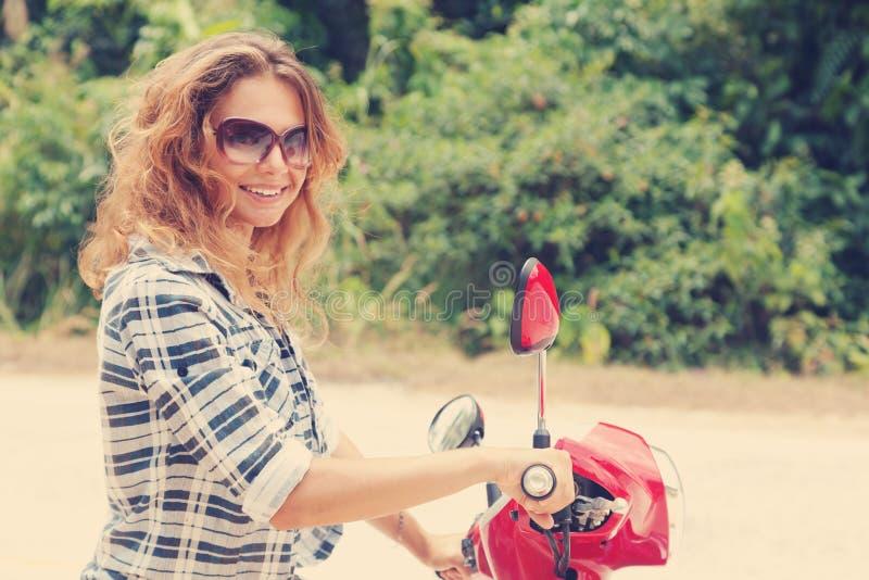 Όμορφη νέα γυναίκα σε μια κόκκινη μοτοσικλέτα στοκ εικόνες