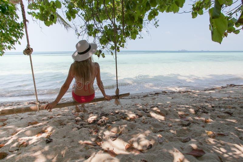 Όμορφη νέα γυναίκα σε μια ταλάντευση που στηρίζεται στην εξωτική παραλία wellness lifestyle στοκ εικόνες