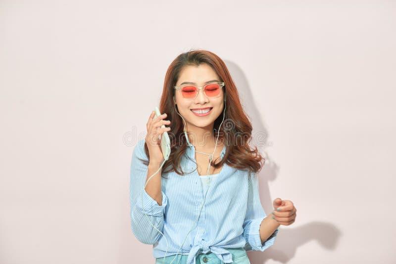 Όμορφη νέα γυναίκα στα ακουστικά που ακούνε τη μουσική και που τραγουδούν στο ελαφρύ υπόβαθρο στοκ εικόνα