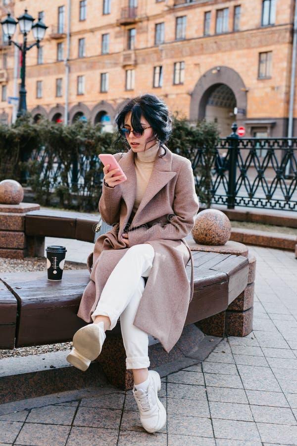 Όμορφη νέα γυναίκα στα γυαλιά ηλίου χρησιμοποιώντας το smartphone της και κοιτάζοντας μακριά στην πόλη στοκ εικόνες