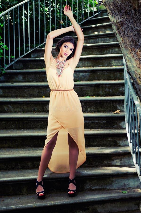 Όμορφη νέα γυναίκα στα σκαλοπάτια κήπων. στοκ εικόνες