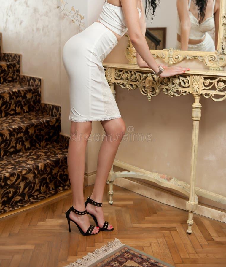 Όμορφη νέα γυναίκα στην απότομα άσπρη σφιχτή κατάλληλη φούστα και κορσές που εξετάζει τον καθρέφτη Τέλειο θηλυκό σωμάτων μπροστά  στοκ φωτογραφίες με δικαίωμα ελεύθερης χρήσης