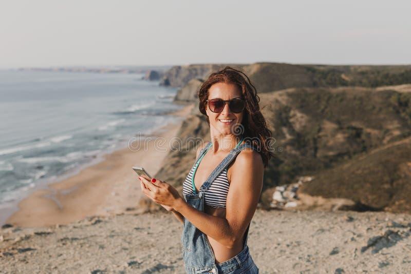 Όμορφη νέα γυναίκα στην κορυφή ενός λόφου που χρησιμοποιεί το κινητά τηλέφωνο και το χαμόγελό της r lifestyle στοκ εικόνα