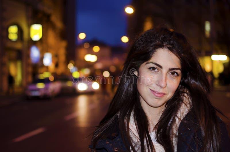 Όμορφη νέα γυναίκα στην οδό νύχτας Φω'τα νύχτας οδών στοκ εικόνες