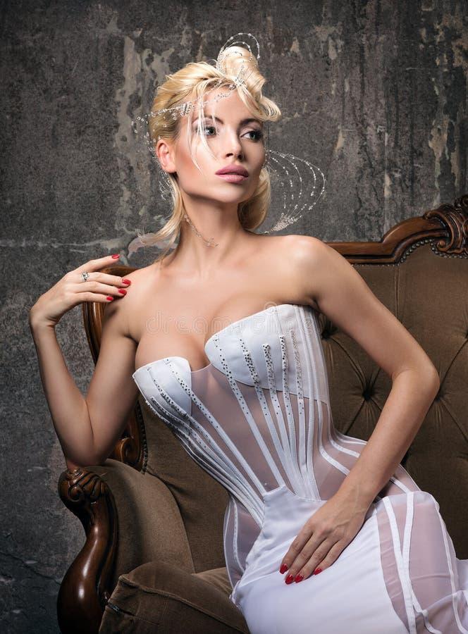 Όμορφη νέα γυναίκα στη συνεδρίαση τρόπου πρωτοπορίας σε έναν κλασικό καναπέ στοκ εικόνα