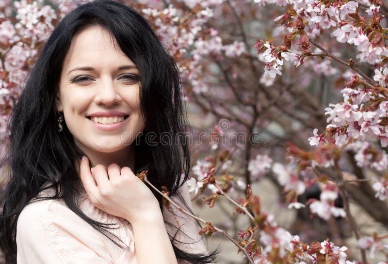 Όμορφη νέα γυναίκα στον κήπο ανθών στοκ εικόνα