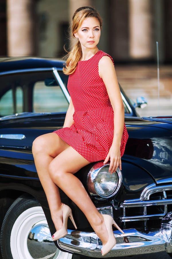 Όμορφη νέα γυναίκα στο εκλεκτής ποιότητας φόρεμα με το αναδρομικό αυτοκίνητο στοκ εικόνα