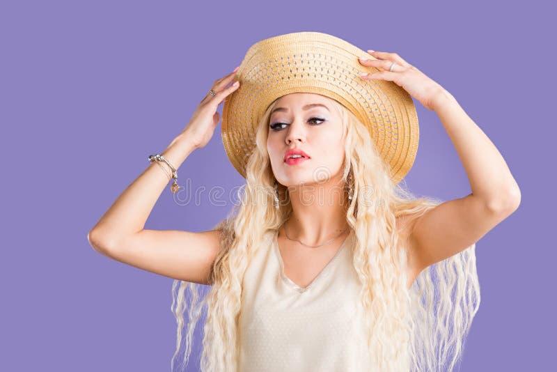 Όμορφη νέα γυναίκα στο καπέλο ήλιων στο πορφυρό υπόβαθρο στοκ εικόνα με δικαίωμα ελεύθερης χρήσης