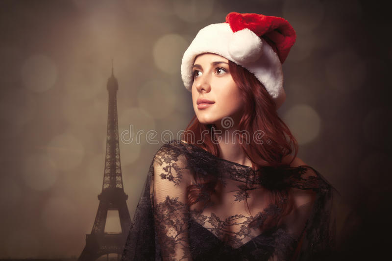 Όμορφη νέα γυναίκα στο καπέλο Άγιου Βασίλη που στέκεται μπροστά από το wo στοκ εικόνα με δικαίωμα ελεύθερης χρήσης