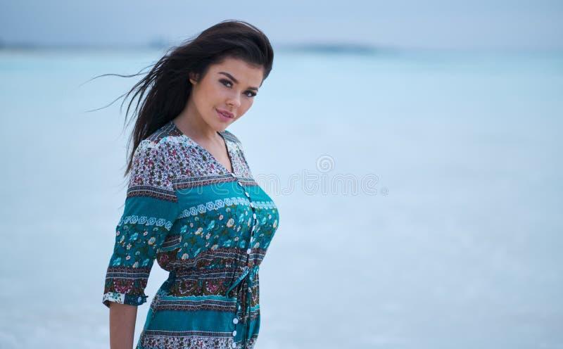 Όμορφη νέα γυναίκα στο κομψό φόρεμα στην παραλία στοκ εικόνα
