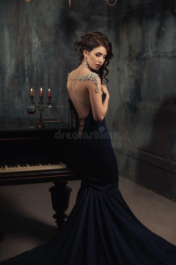 Όμορφη νέα γυναίκα στο μαύρο φόρεμα δίπλα σε ένα πιάνο με τα κεριά κηροπηγίων και κρασί, σκοτεινή δραματική ατμόσφαιρα του κάστρο στοκ φωτογραφίες με δικαίωμα ελεύθερης χρήσης