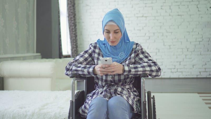 Όμορφη νέα γυναίκα στο με ειδικές ανάγκες άτομο hijab που χαμογελά, αναπηρική καρέκλα, στο διαμέρισμα στοκ φωτογραφίες