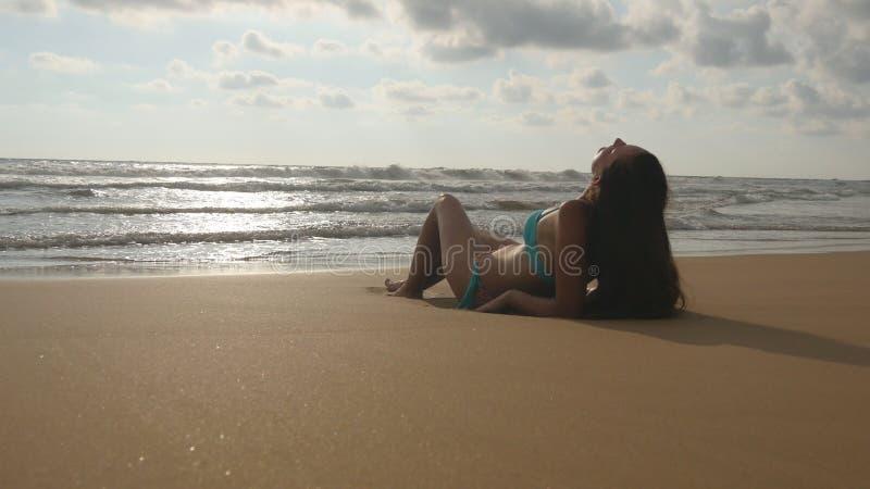 Όμορφη νέα γυναίκα στο μπικίνι που βρίσκεται στη χρυσή άμμο στην παραλία θάλασσας και που χαλαρώνει κατά τη διάρκεια του ταξιδιού στοκ εικόνα