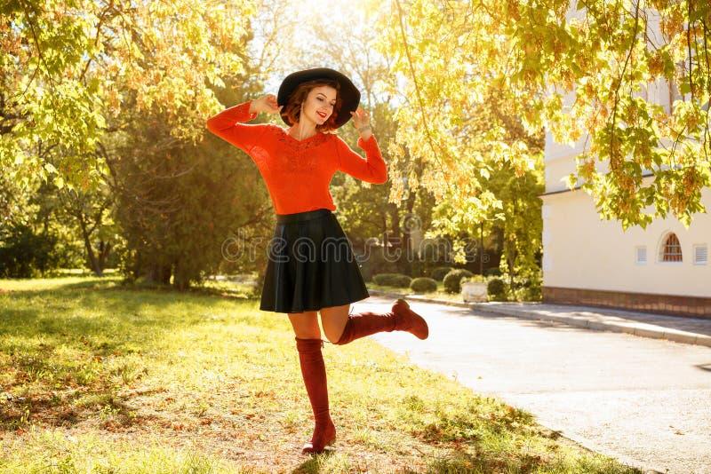 Όμορφη νέα γυναίκα στο πάρκο φθινοπώρου στο μαύρο καπέλο στοκ φωτογραφία με δικαίωμα ελεύθερης χρήσης