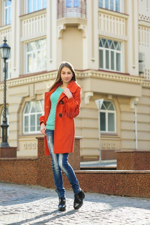 Όμορφη νέα γυναίκα στο παλτό που περπατά κάτω από την οδό στοκ εικόνα με δικαίωμα ελεύθερης χρήσης