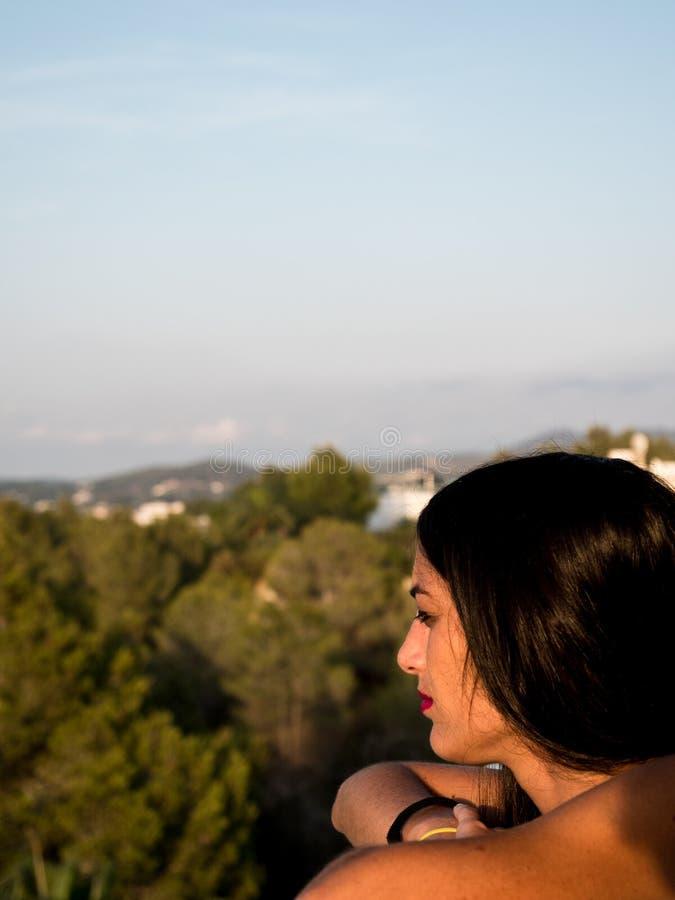Όμορφη νέα γυναίκα στο σχεδιάγραμμα που κοιτάζει από ένα μπαλκόνι στον ορίζοντα με τα μέρη της βλάστησης γύρω από την στοκ φωτογραφία με δικαίωμα ελεύθερης χρήσης